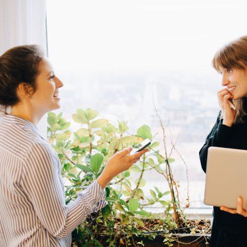 Två kvinnor som står vid ett fönster och pratar.