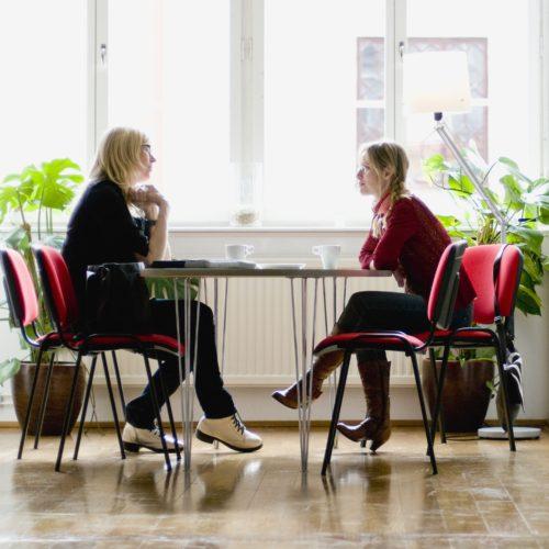 Två kvinnor sitter vid ett bord och samtalar.