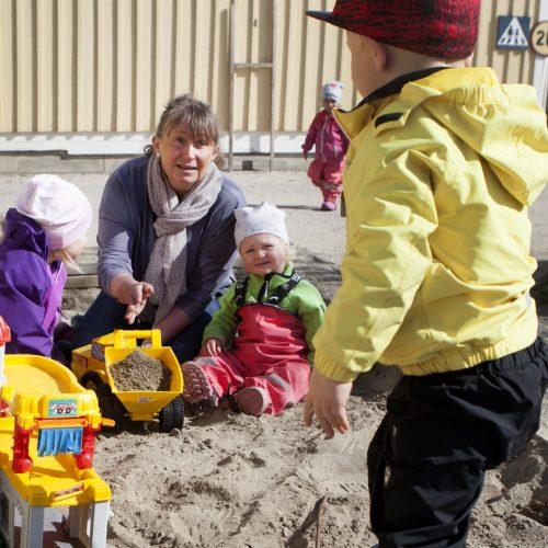 Förskolelärare med fyra barn i en sandlåda.