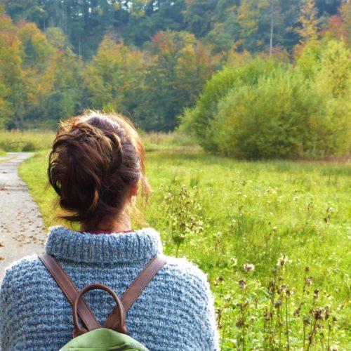 Kvinna bakifrån ute i skogen.